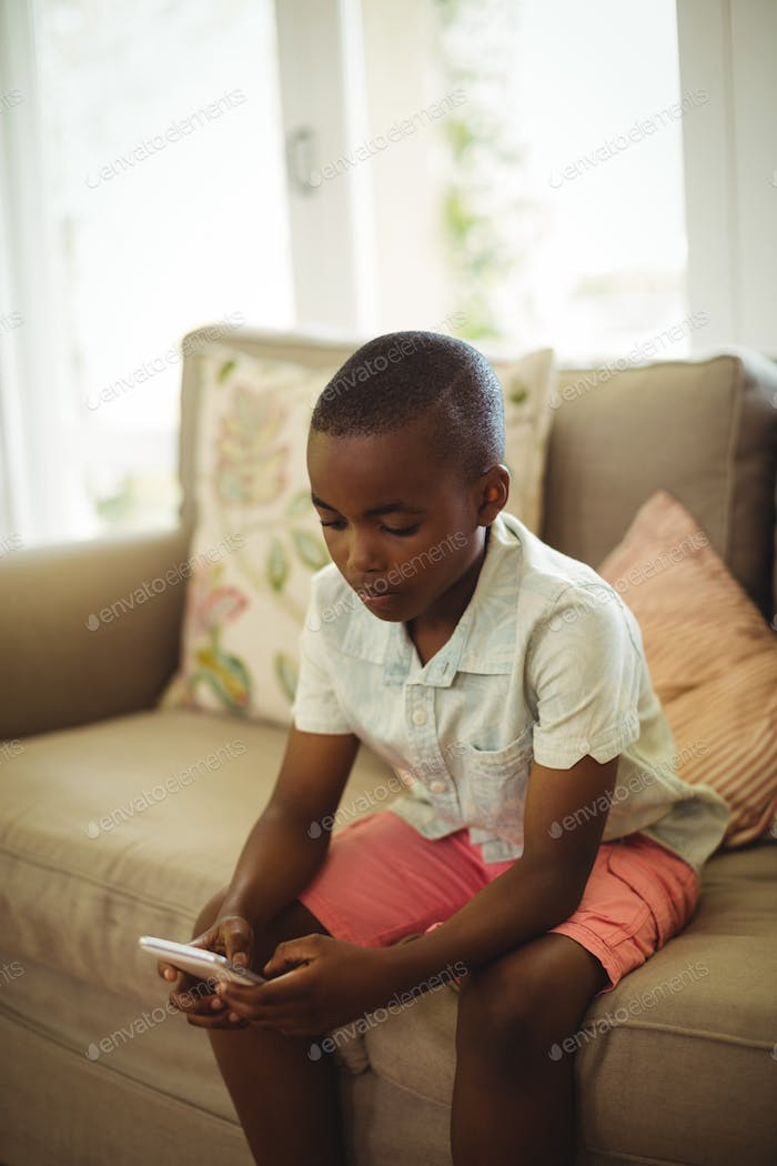 Boy sitting on sofa and using mobile phone in living room