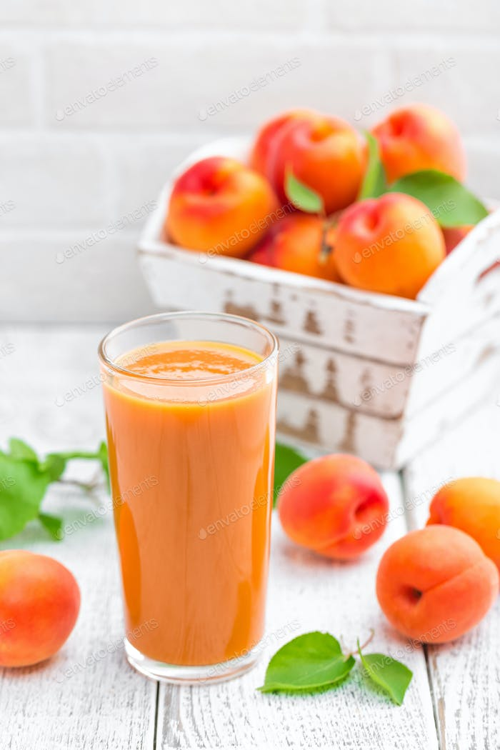 Apricot juice and fresh fruits with leaves