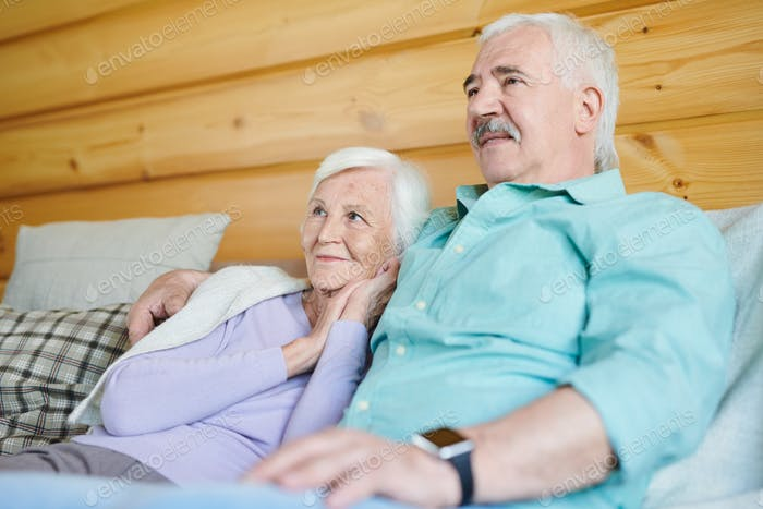 Happy mature man and his wife watching television together