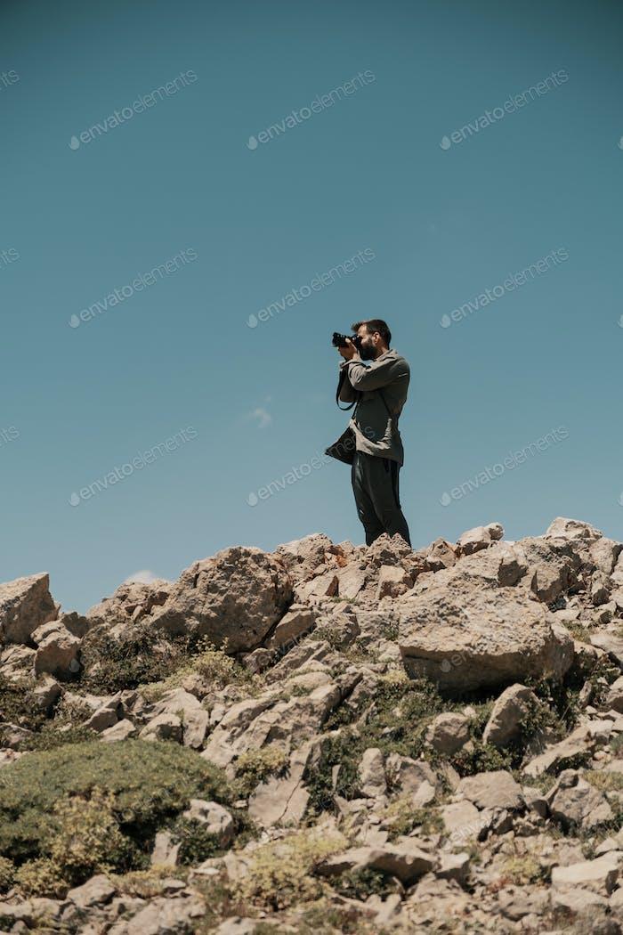 Man taking photos on a rocky mountain