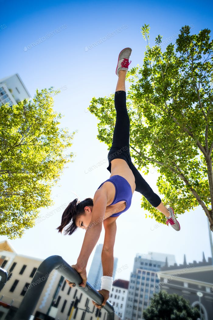 Athletic woman performing handstand on bar in the city