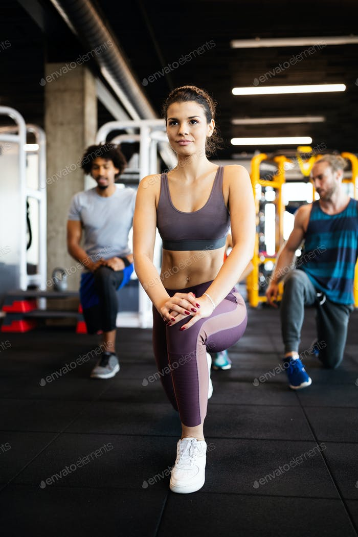 Healthy young athletes friends doing exercises at gym