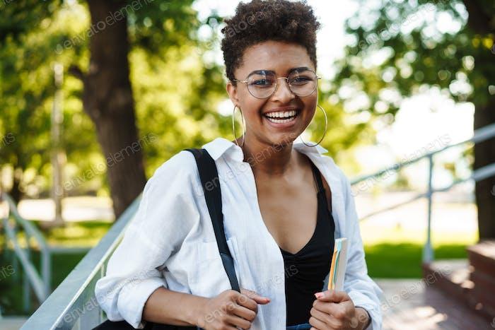 Atractivo joven joven estudiante africana caminando
