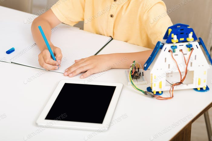 Little scientist working on robotic project, taking notes