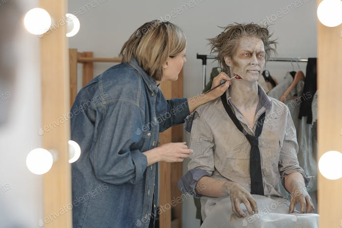 Reflection in mirror of female visage artist applying zombie makeup on face and neck of young man