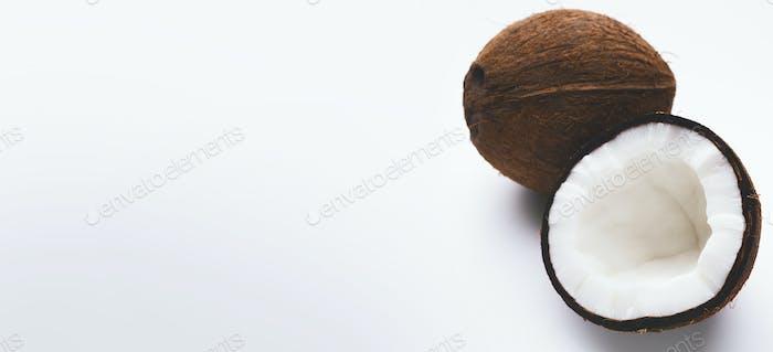Ganze und halbe Kokosnuss auf weiß