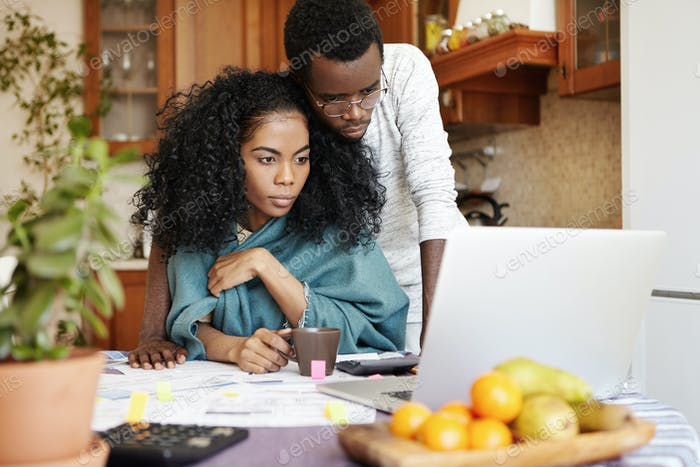 Young dark-skinned couple using generic laptop pc while managing family budget, calculating expenses