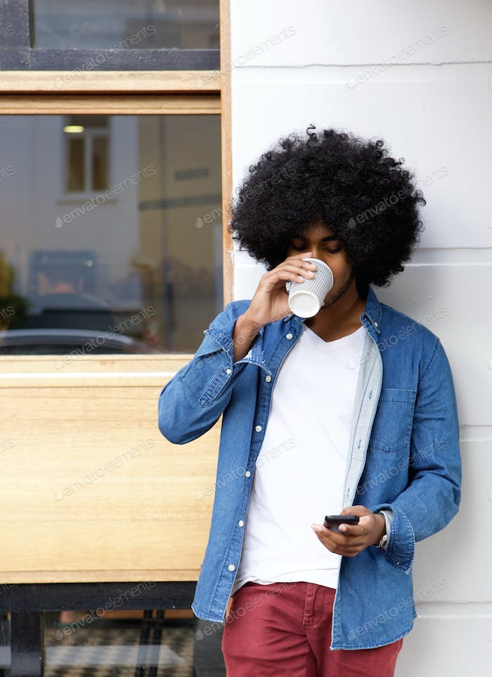 Cool guy drinking coffee and using cellphone