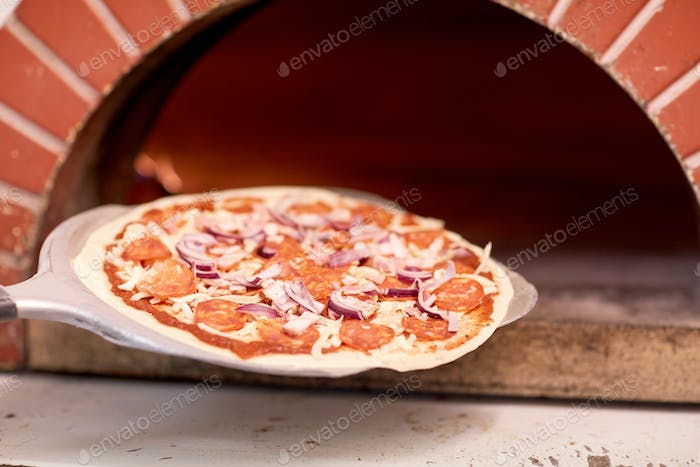 peel placing pizza into oven at pizzeria