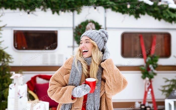 Winter Camping. Glückliche lachende Mädchen genießen Tasse Tee in der Nähe von Wohnmobil im Freien