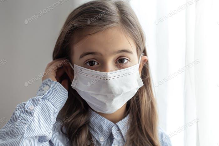 Kleines Mädchen trägt eine medizinische Schutzmaske gegen Coronavirus aus nächster Nähe.