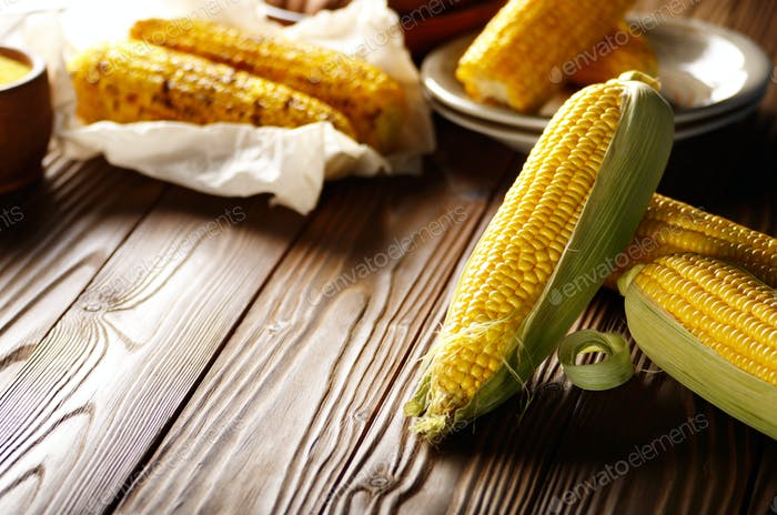 Kitchen table with raw and grilled sweet corn cob on baking pape