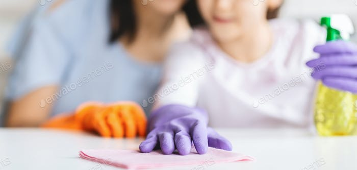Little girl and her mom cleaning table surface from dust