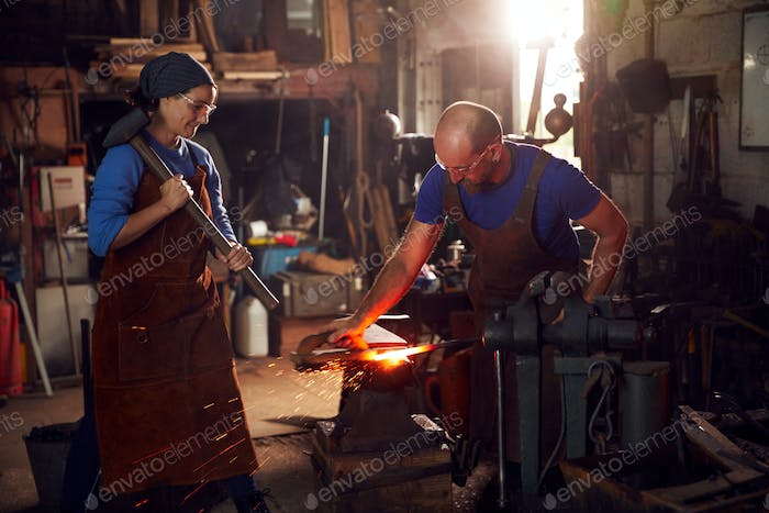 Male And Female Blacksmiths Hammering Metalwork On Anvil With Sparks