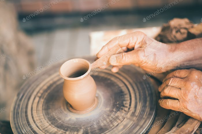 Potter sculpts a clay pot