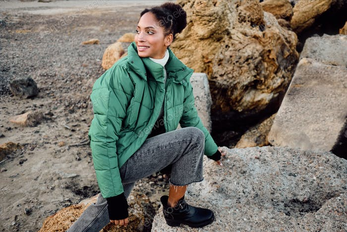 Stylish African American girl in down jacket happily looking away climbing on stones by the sea