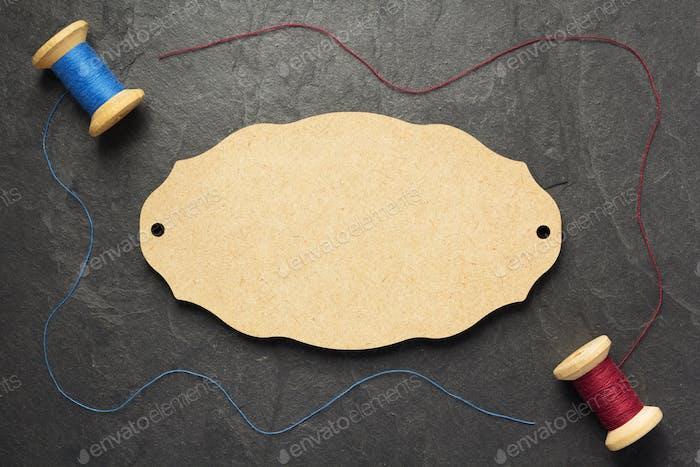 Fadenspule und Nadel auf Schieferstein