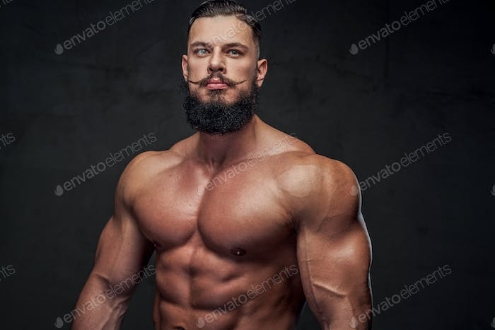 Handsome athlete with beard posing in gray background