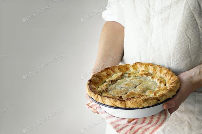 Baker holding a freshly baked cherry pie yummy dessert