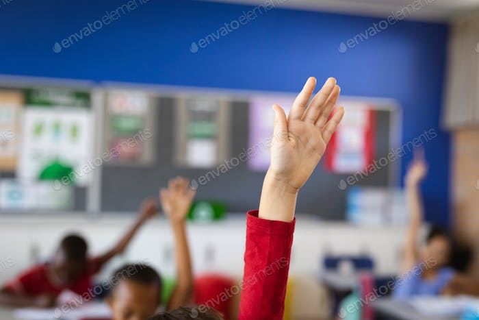Raised hand of caucasian boy for participation in the class at elementary school