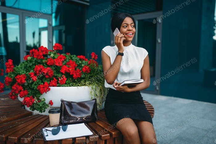 Business lady talks by phone and looks at the time