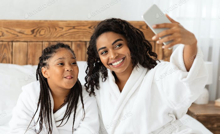 Selfie Fun. Cheerful Mom And Daughter In Bathrobes Taking Photo On Smartphone