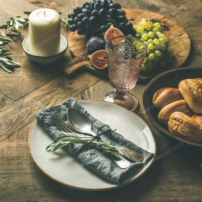 Plate with linen napkin, fork, spoon, glass, candle, fruits, bread