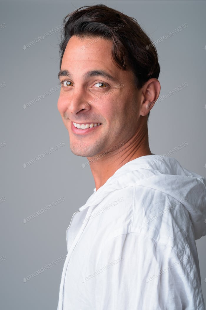 Closeup profile view of happy handsome Hispanic man looking at camera