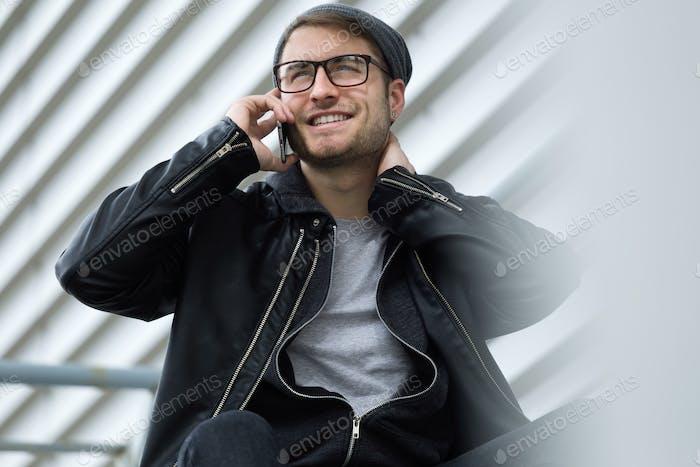 Joven moderno hablando por teléfono en la calle.