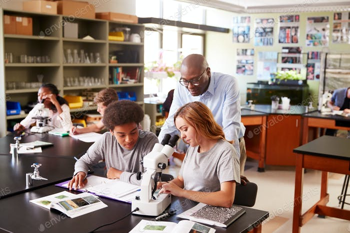 High School Students With Tutor Using Microscope In Biology Class