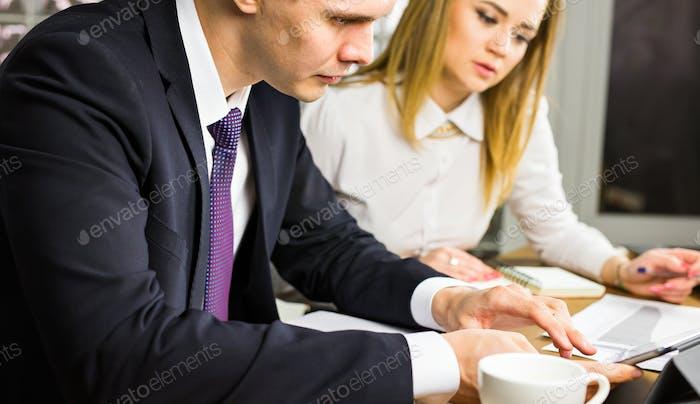Zwei Büroangestellte sprechen in einem Büroinnenraum