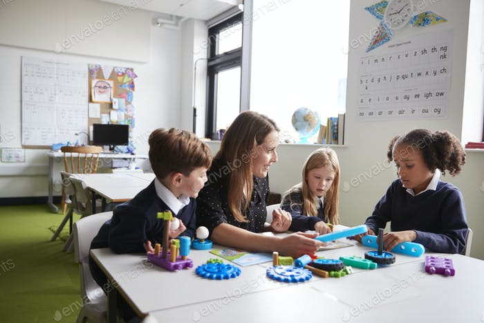 Female teacher and three primary school kids working with educational construction toys