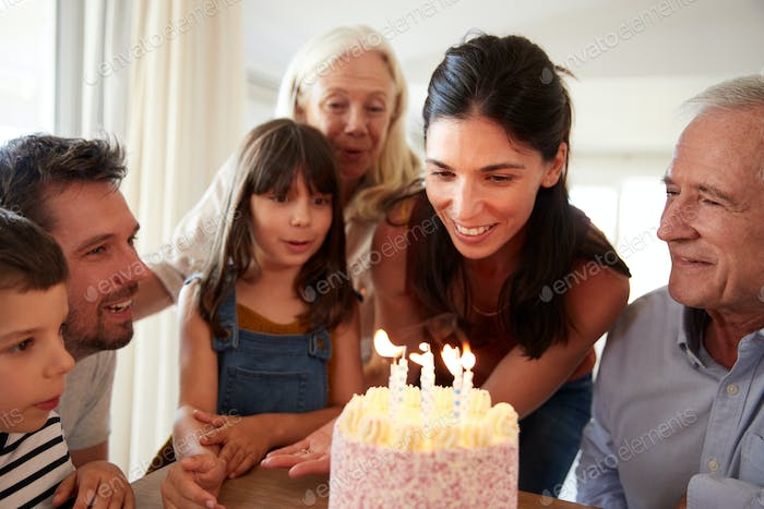 Six year old girl blowing out the candles on birthday cake watched by her mum and family, close up