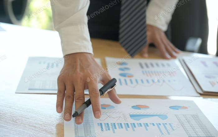 The management is checking the company earnings chart on the office desk.