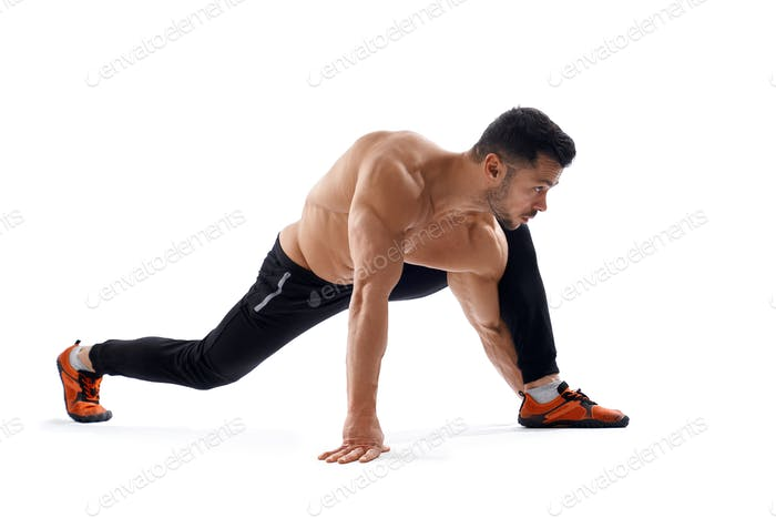 Hombre musculoso sin camisa estirando las piernas