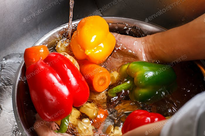 Hands wash vegetables in basin.