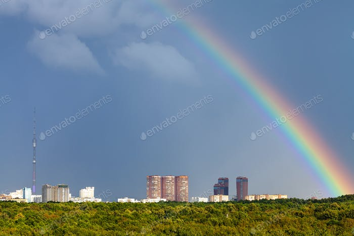 rainbow in rainy sky over city with TV tower