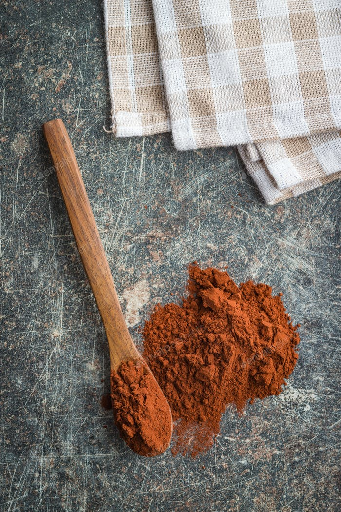 Tasty cocoa powder in wooden spoon.