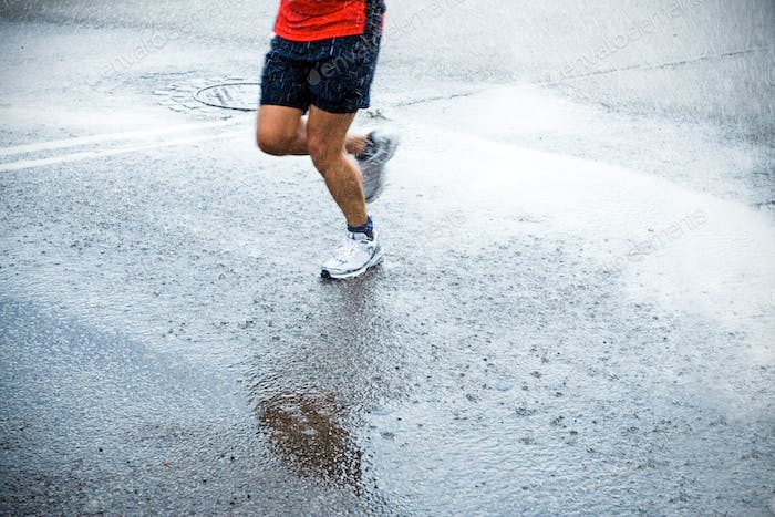 Marathon runner in rain on city street