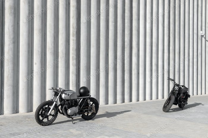 two motocycles in front of the wall