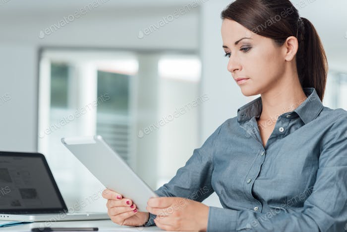Confident businesswoman using a digital tablet