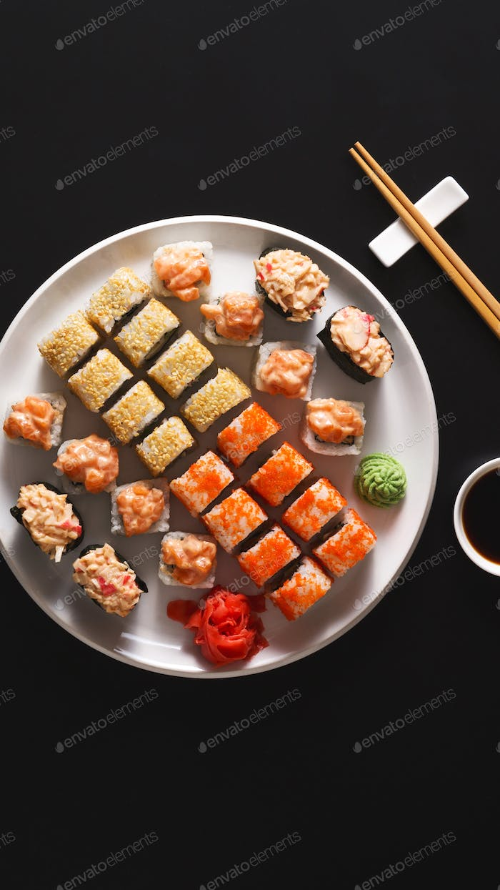 Handmade sushi and rolls on white plate with wooden sticks