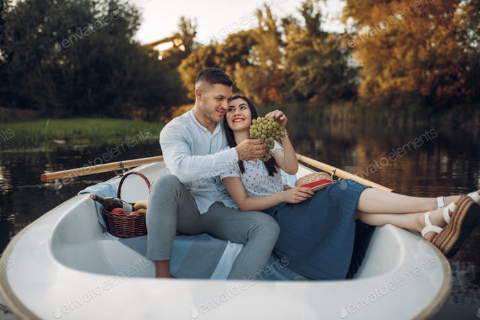 Love couple hugs in a boat on quiet lake