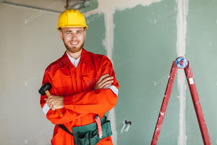 Smiling builder in orange work clothes and hardhat holding hamme