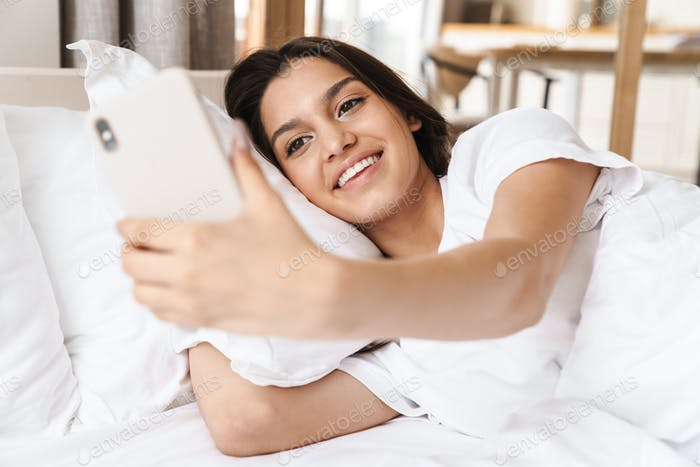 Photo of smiling woman taking selfie on smartphone while lying in bed