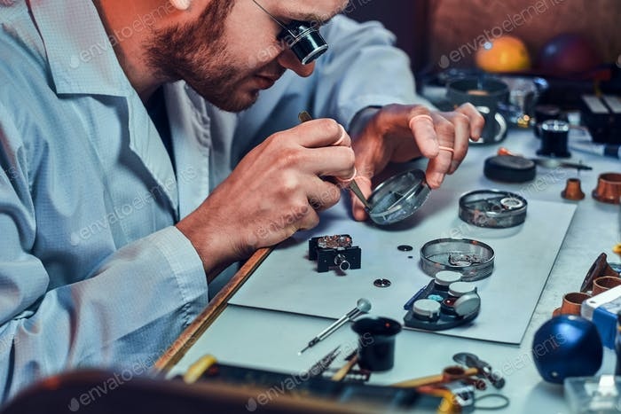 Expirienced clockmaster is fixing old watch for a customer at his repairing workshop