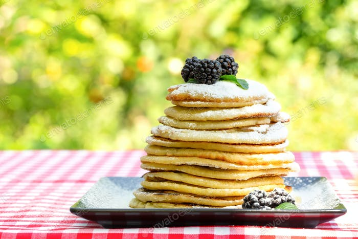 Pancakes with blackberries and icing sugar on green background