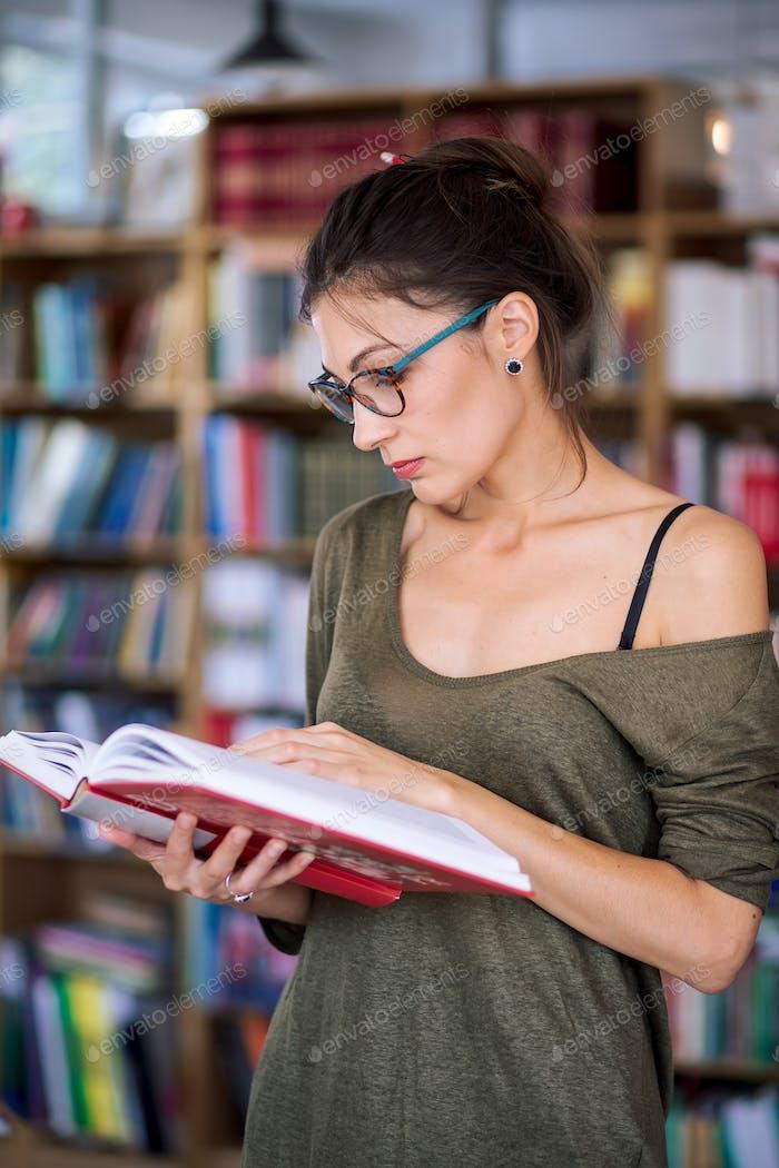 Joven mujer simpática leyendo un libro