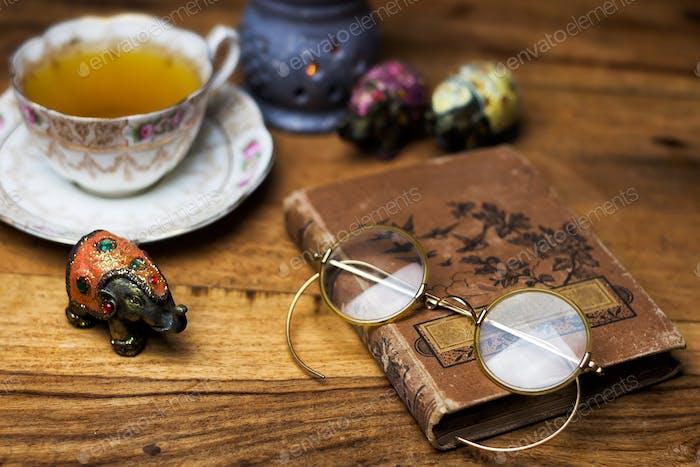 viejo libro en el escritorio de madera, gafas vintage, taza de porcelana de té y platillo
