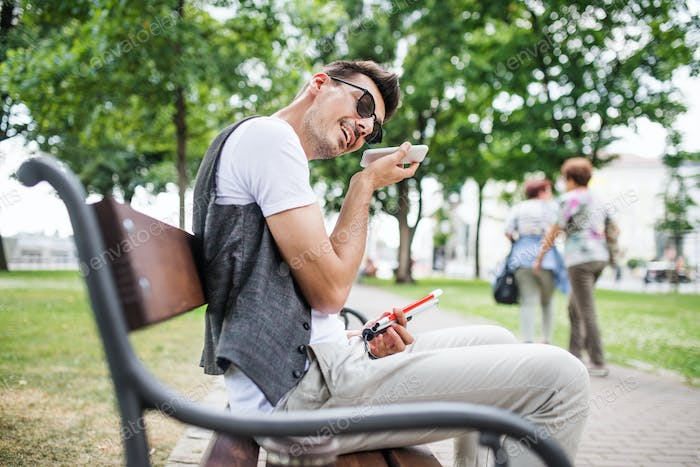Young blind man with smartphone sitting on bench in park in city